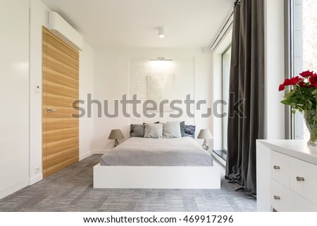 White cosy minimalist bedroom with comfortable double bed
