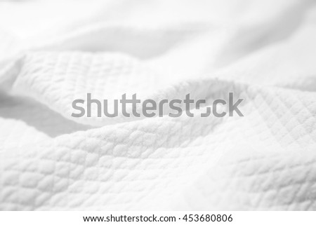 White cotton fabric texture, crumpled blanket, background photo with selective focus
