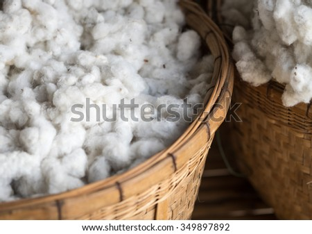 White cotton wool in bamboo basket for fabric with selective focused point - stock photo