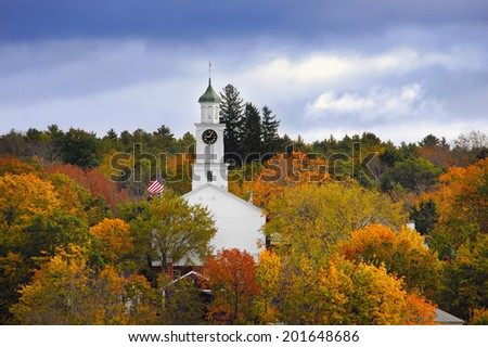 White country church and American flag surrounded by autumn colors in New England - stock photo