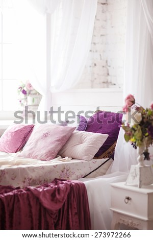 White cozy bed with vintage pillow and flowers - stock photo