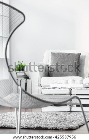 White cozy lounge in scandinavian style with fancy stylish armchair and fluffy soft carpet on the floor - stock photo