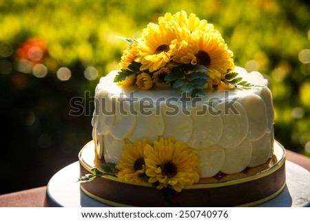white creamy delicious cake decorated with yellow flowers and green leafs - stock photo