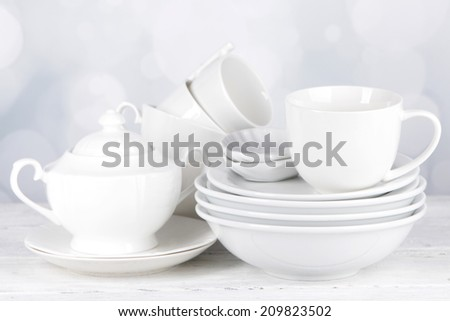 White crockery and kitchen utensils, on wooden table, on light background - stock photo