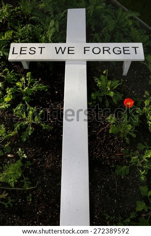 white cross in a garden to remember the fallen heroes of war - stock photo