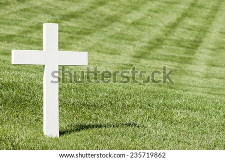 White cross on green lawn.Arlington National Cemetery, - stock photo