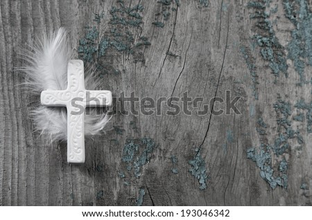 White cross with feather on an old rustic background. - stock photo