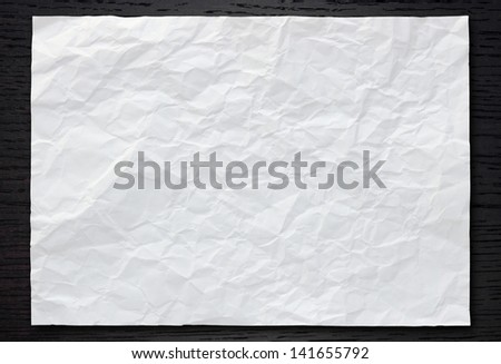 White crumpled paper on dark wood background - stock photo