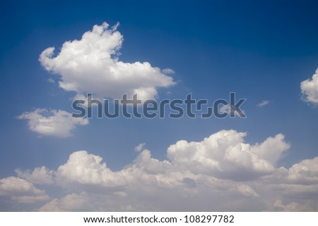 White cumulus clouds and a blue sky - stock photo