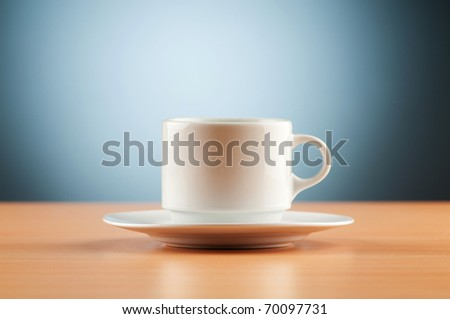 White cup against colourful gradient on the table - stock photo