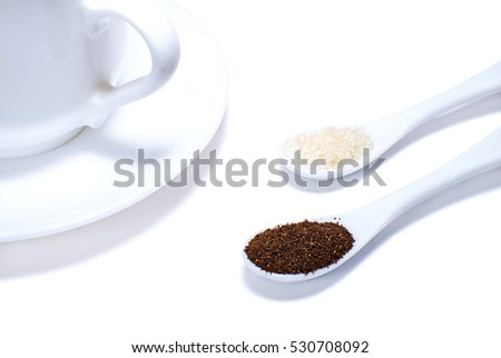 White cup and ceramic spoons with sugar and ground coffee