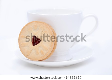 White cup and cookie on the saucer on the white background