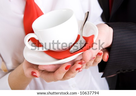 white cup in hands of the girl and a man in business wear