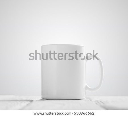 White cup mock-up inclined in center of wooden table