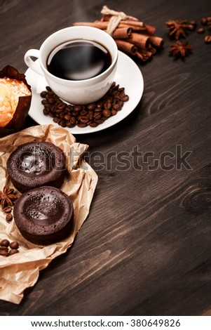 White cup of black coffee for breakfast with coffee beans and spices are standing on dark wooden table with pastry: cookies, brownie and muffin. Place for text - stock photo