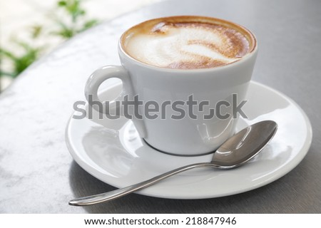 White cup of cappuccino stands on the table, selective focus - stock photo