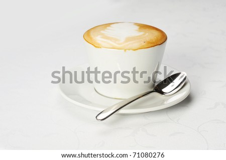 White cup of cappuccino with brown and white foam on top. Object  on white - stock photo
