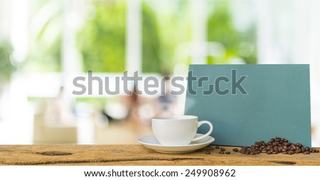 White cup of coffee and green chalkboard on wooden bar with blur image of people sit in living room .