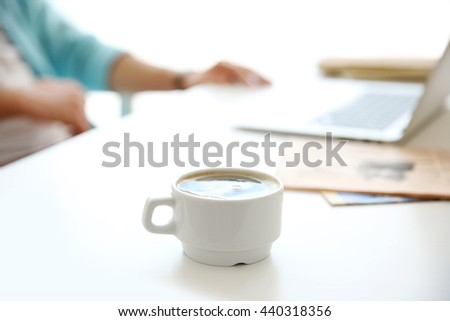 White cup of coffee and man working on background - stock photo