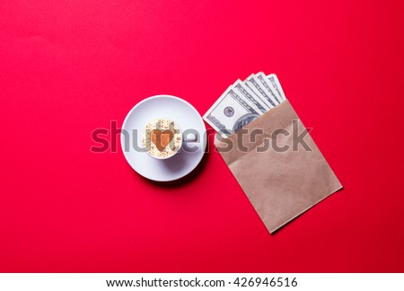 white cup of coffee and money in the envelope on the red background - stock photo