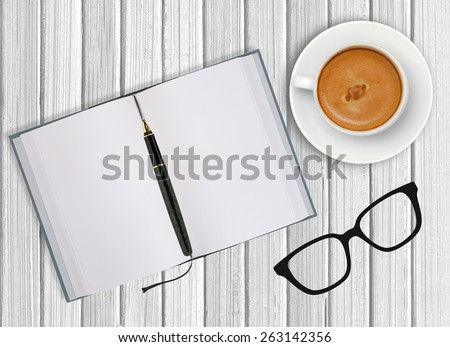White cup of coffee and opened blank notebook on wooden background - stock photo