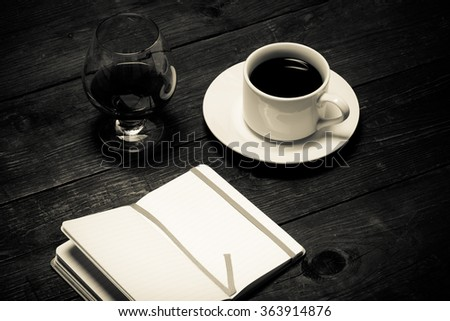 White cup of coffee, cognac in a glass and notebook on old wooden table. Toned.