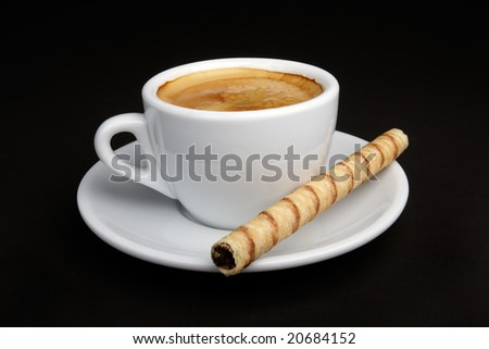 White cup of coffee (espresso) with rolled wafer. - stock photo