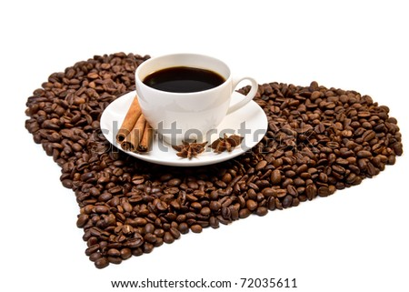 White cup of coffee on heart shaped coffee beans with three sticks of cinnamon and star anise fruits - stock photo