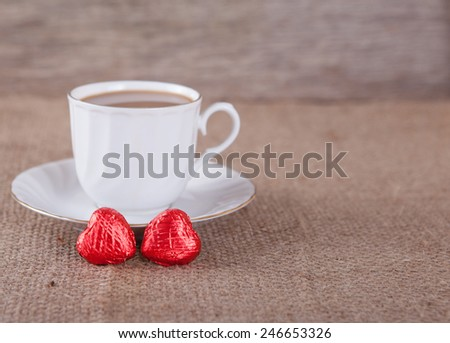 White cup of coffee with chocolate, rustic background - stock photo
