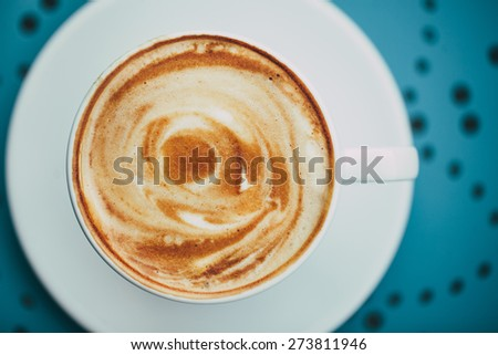 White cup of coffee with crema on a round blue table with a  pattern - stock photo