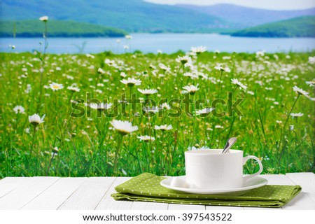 White cup of coffee with napkin on white wooden table against defocused spring green blooming meadow and lake. - stock photo