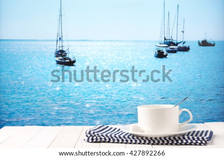 White cup of coffee with napkin on white wooden table against defocused sunny sea with yachts. - stock photo