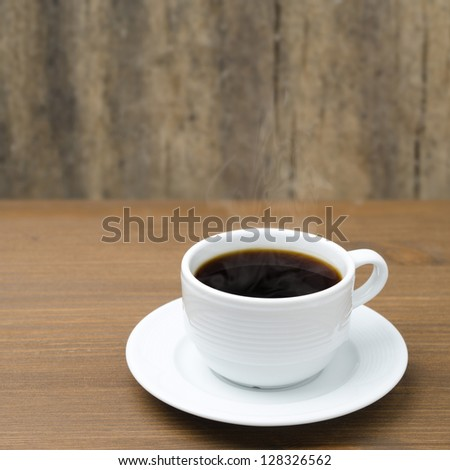 white cup of coffee with steam on a wooden table - stock photo