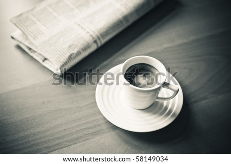 white cup of Espresso with Newspaper, vintage monochrome
