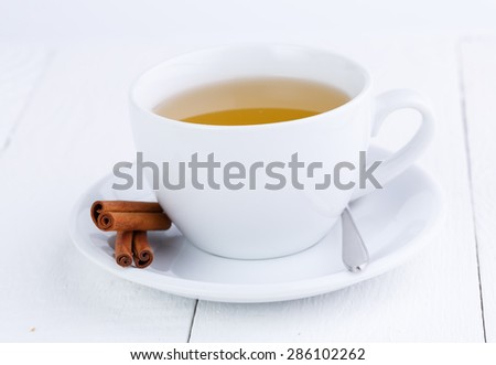 White cup of green tea and cinnamon. - stock photo