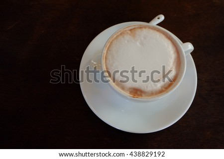 white cup of hot chocolate and black wooden background