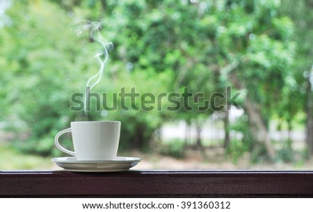 white cup of hot coffee on natural green background, - stock photo