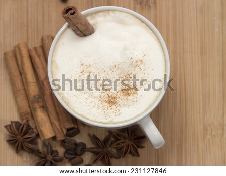 white cup of hot coffee with milk foam, cinnamon, star anise and coffee beans  on the wooden table - stock photo