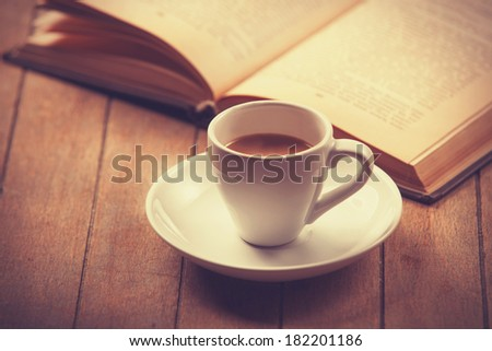 white cup of the coffee and vintage book. Photo with filter as a retro color image style. - stock photo