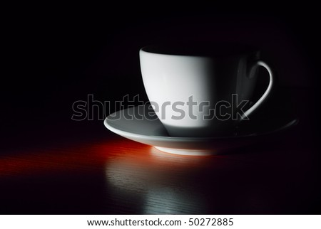 white cup on saucer in dark - stock photo