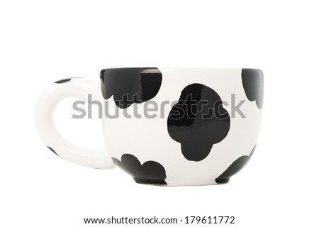 White cup with black cow dots isolated on white