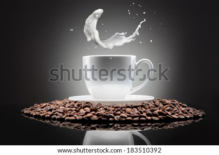 white cup with coffee beans and milk splash on black - stock photo