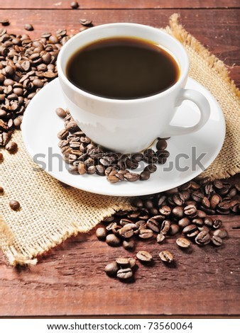 white cup with coffee beans on the wooden table - stock photo