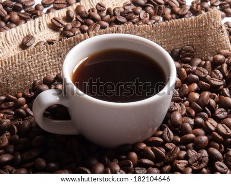 white cup with coffee on burlap background with beans - stock photo