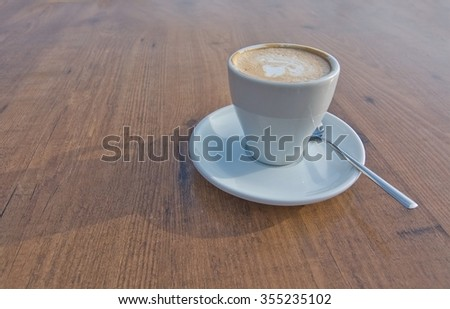 White cup with foaming cappuccino coffee and spoon - stock photo