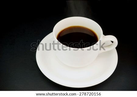 white cup with hot liquid and steam on black - stock photo