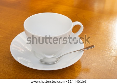 white cup with spoon and saucer on wooden table - stock photo