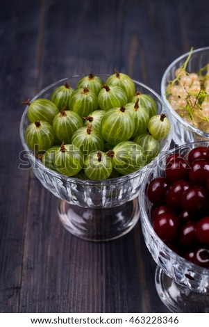 White currant, green gooseberry, cherry, in a bowl on a table