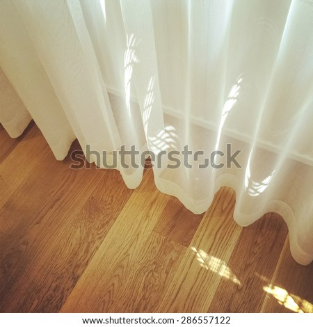 White curtain in a room with wooden floor, light coming through the window. - stock photo