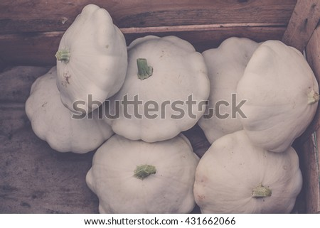 White custard marrows in a wooden box on a farm market. Filtered shot - stock photo